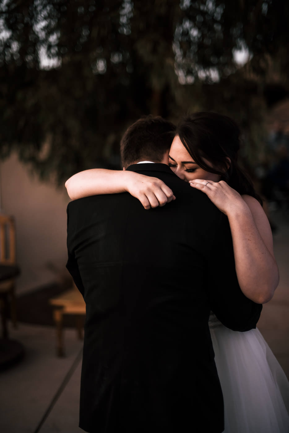 Sweet newlyweds have their first dance as the sun sets.