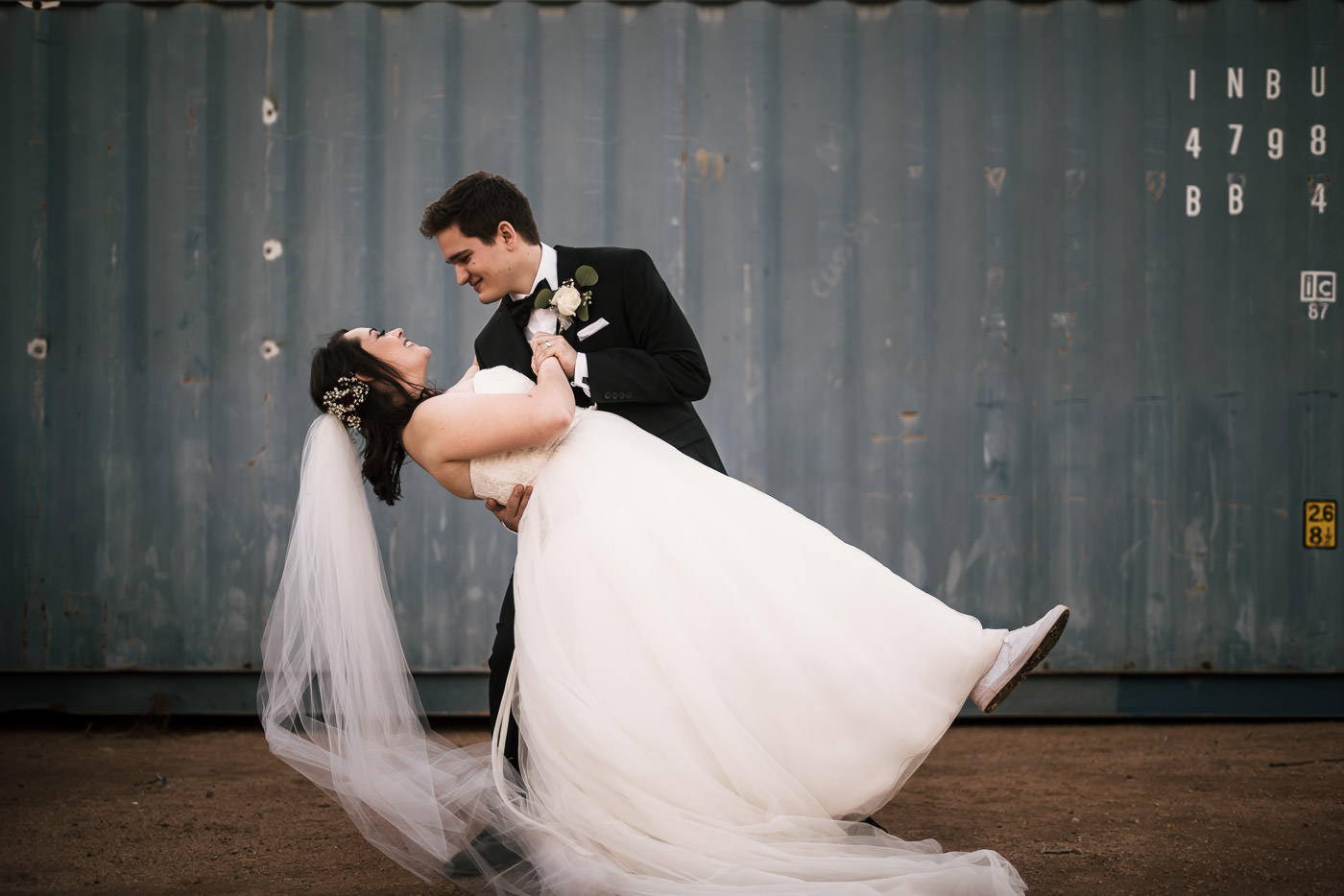 Groom dips his bride after a slow dance at their country wedding.