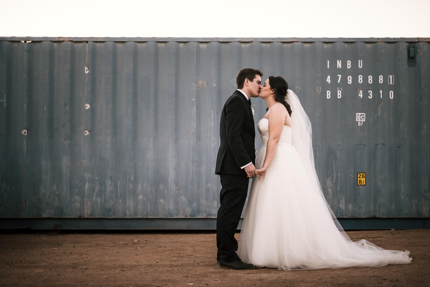 Young couple kisses in front of a blue shipping container at their country wedding in Temecula.