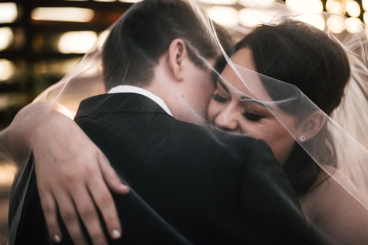 Newlyweds hold each other close under the wedding veil for a romantic moment.
