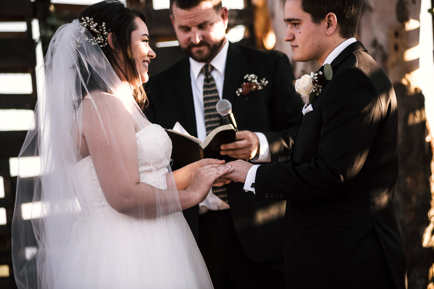 Bride laughs as she places the wedding band on her husbands finger.