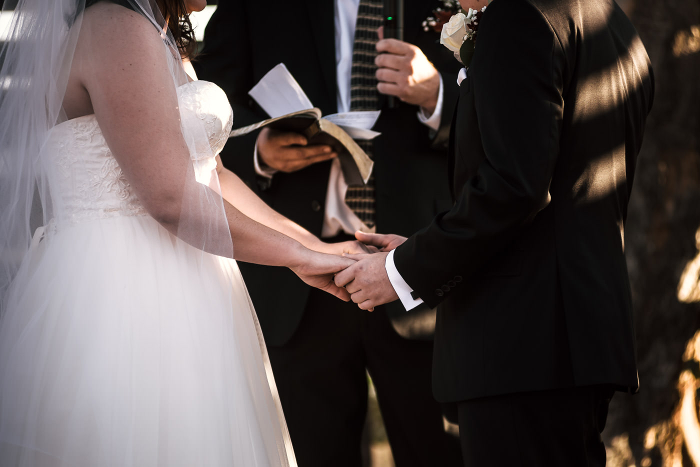 Couple holds hands as they say their vows at their country wedding.