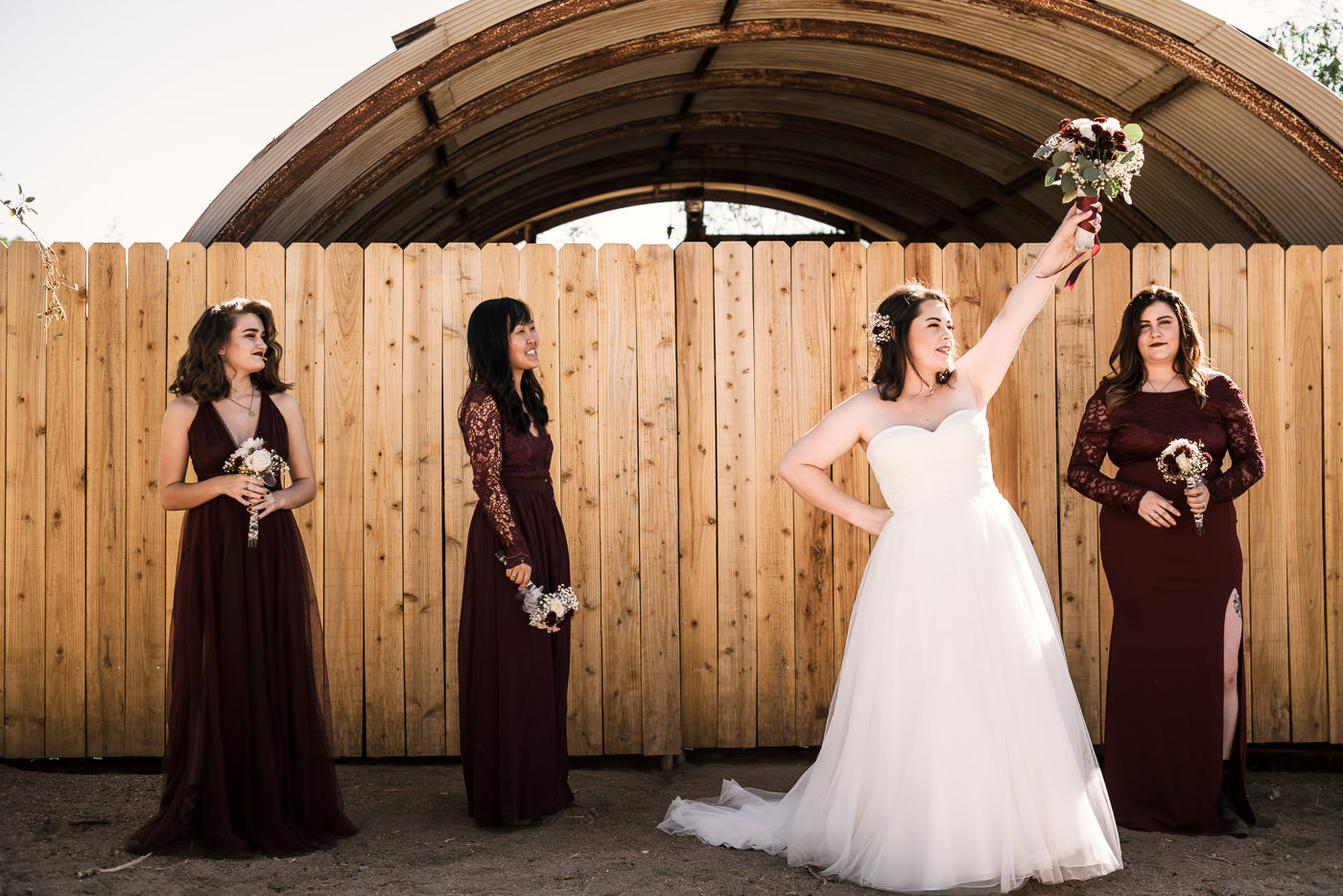 Bride poses with her bridesmaids in front of a wooden wall in Temecula California.