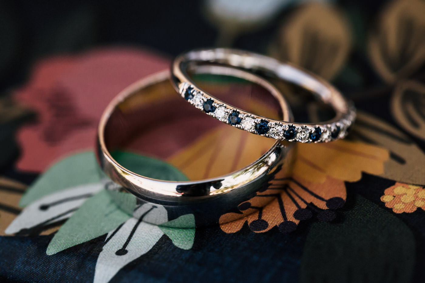 beautiful wedding rings sit atop a floral pattern