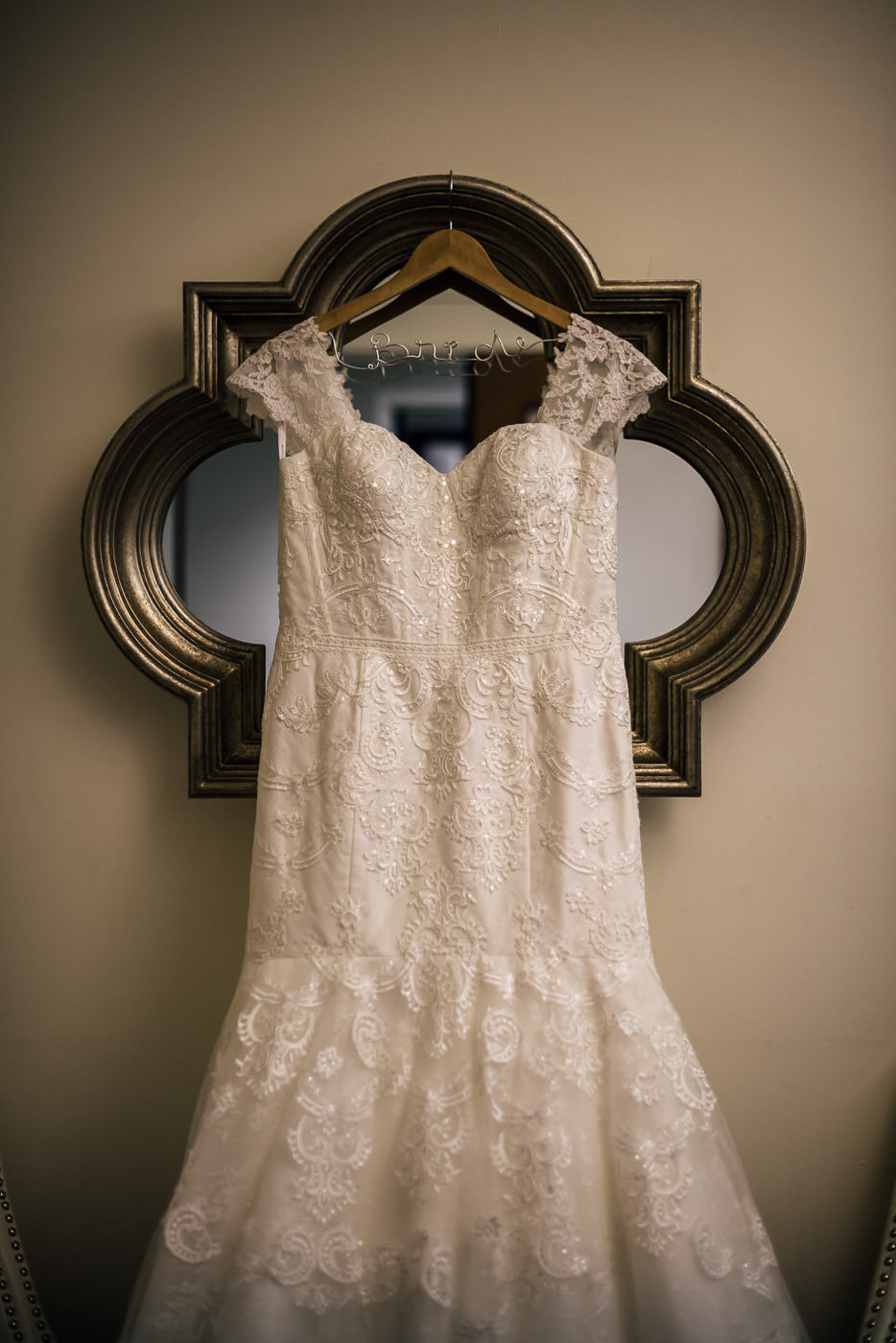 Beautiful wedding dress hung from a mirror at Knollwod Country Club.