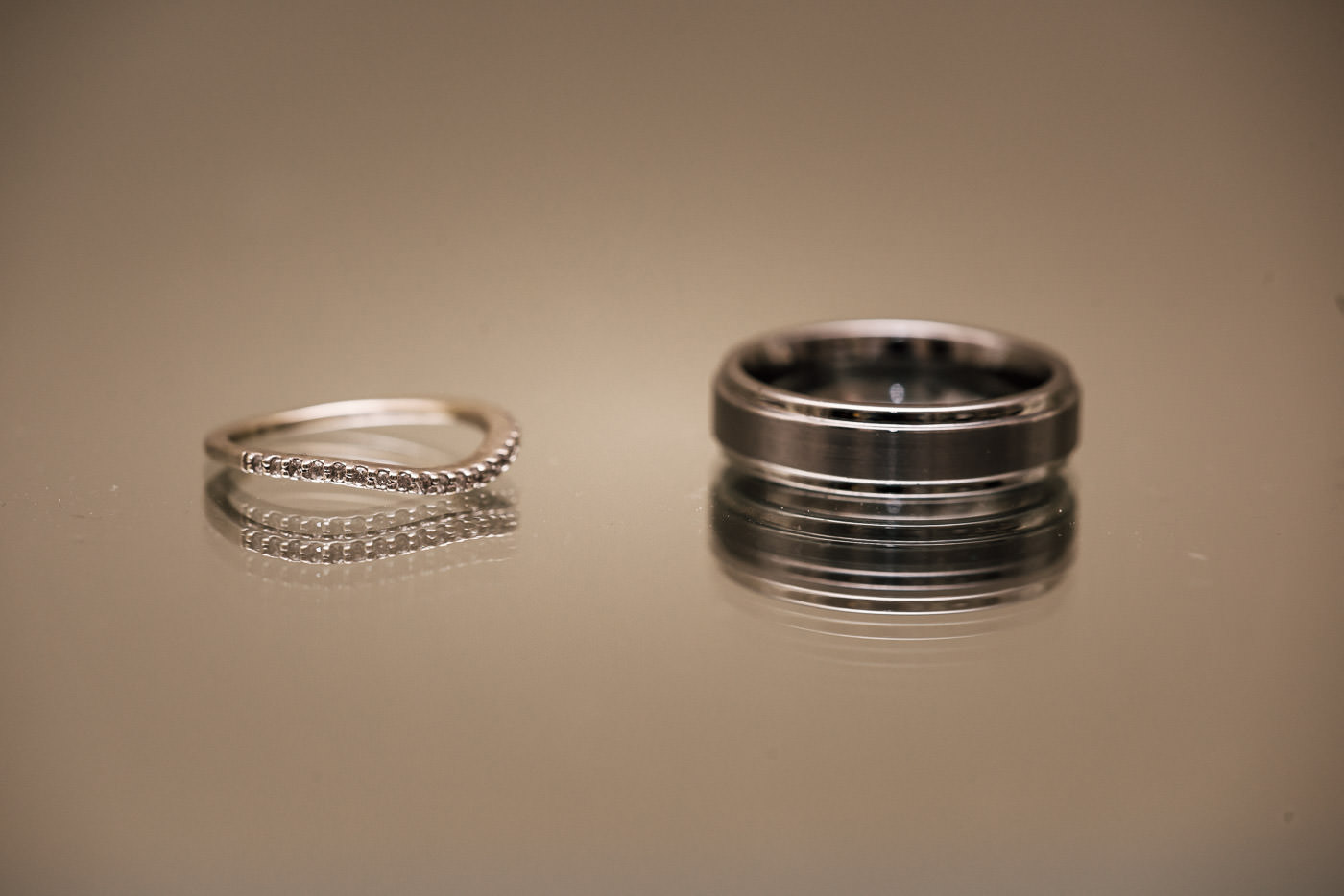 Couples wedding rings reflected n a mirror.