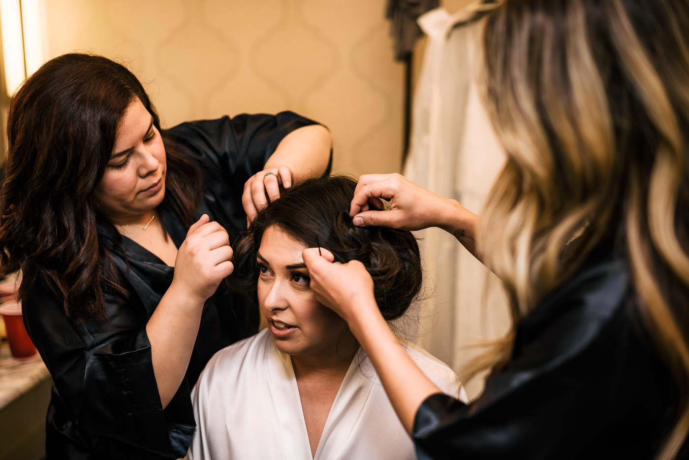 Bridesmaids help bride with her hair before the wedding.