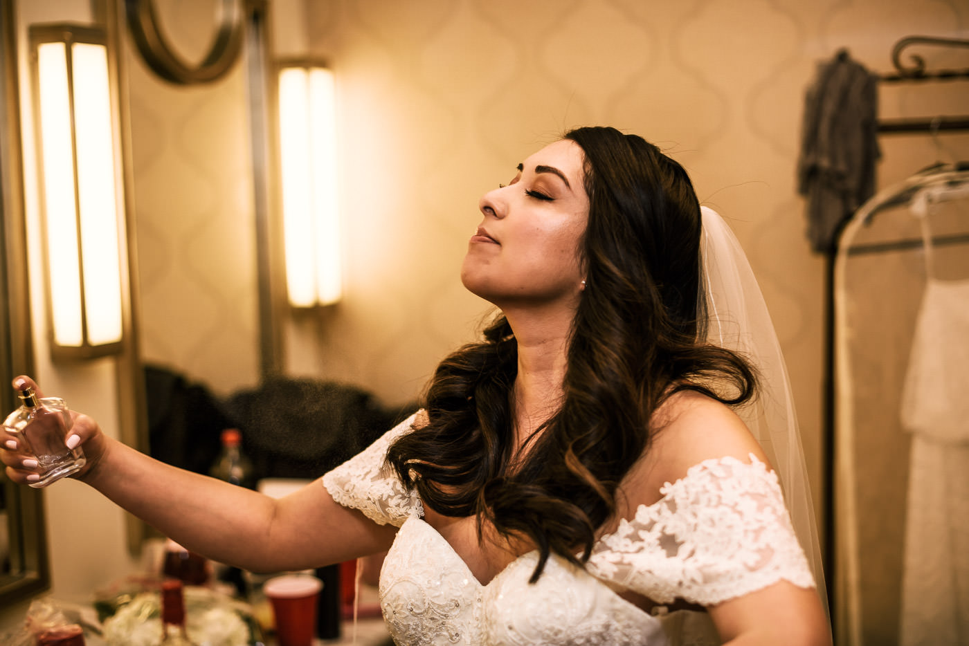 Bride puts on perfume as she prepares for the first look at Knollwod Country Club.