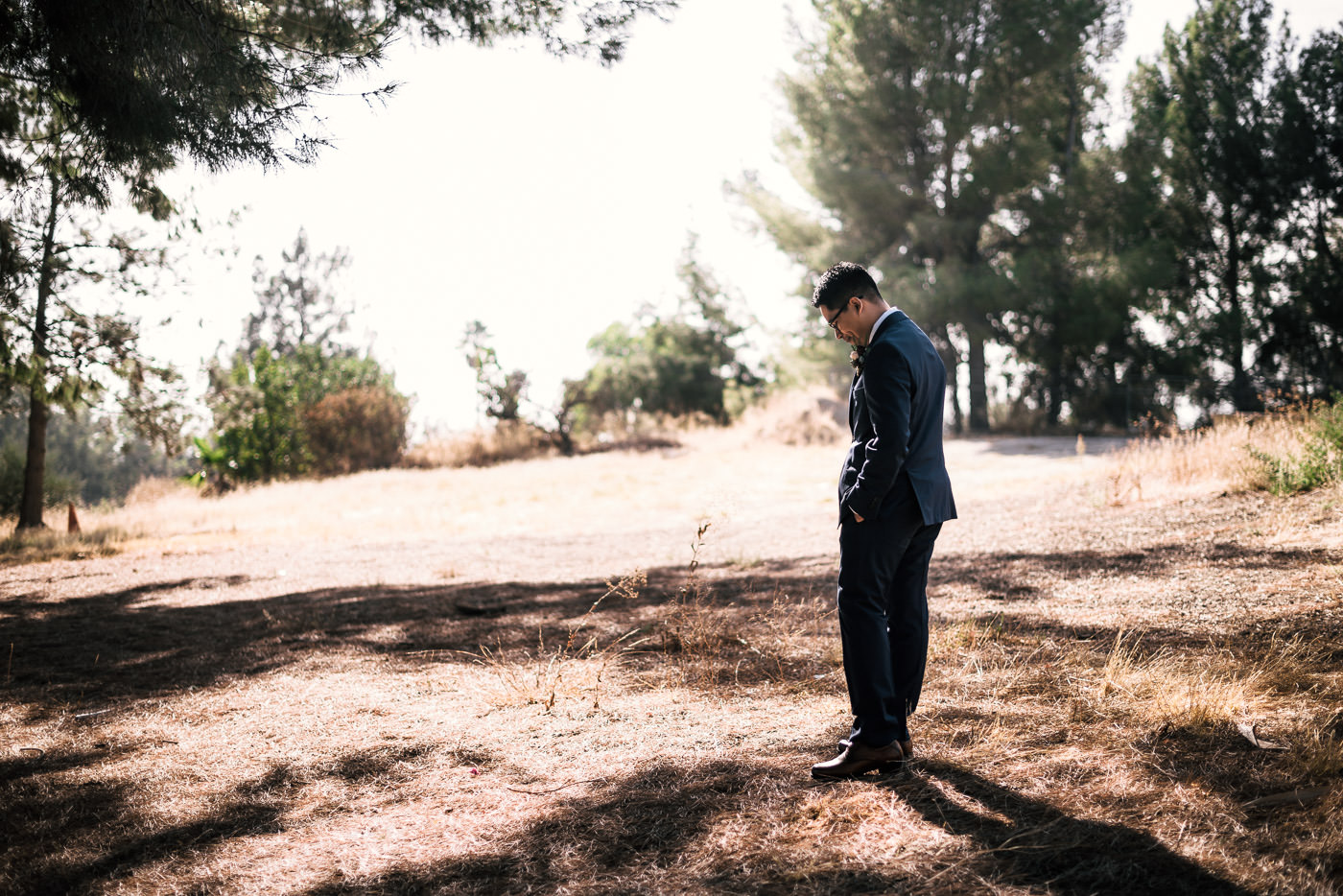Groom anxiously waits in a field for his bride to arrive.