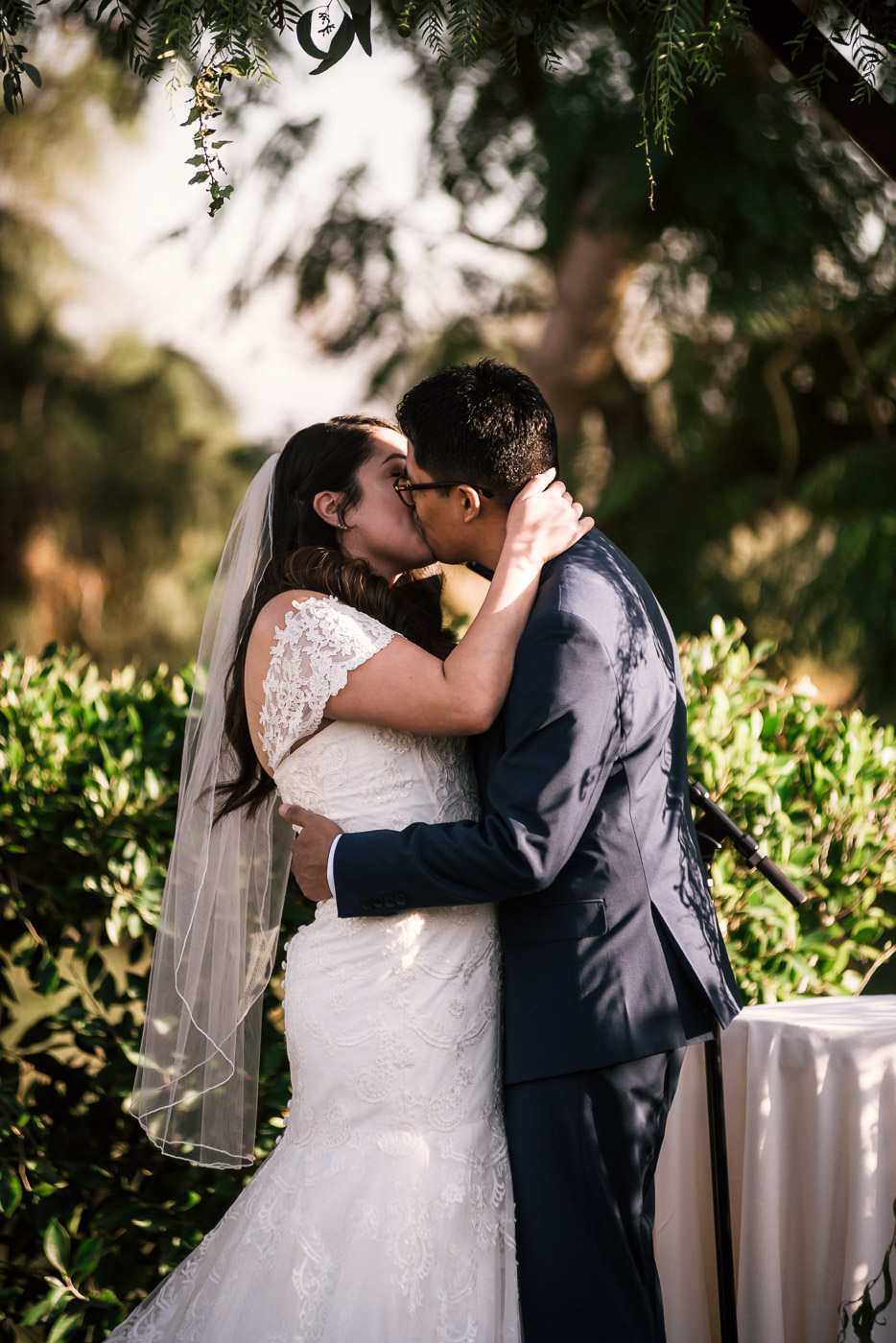 Newlywed couple has their first kiss after their ceremony at the Knollwood Country Club.