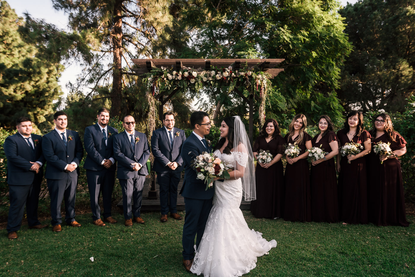 Bride and groom hold each other as they pose for photos with their wedding party.