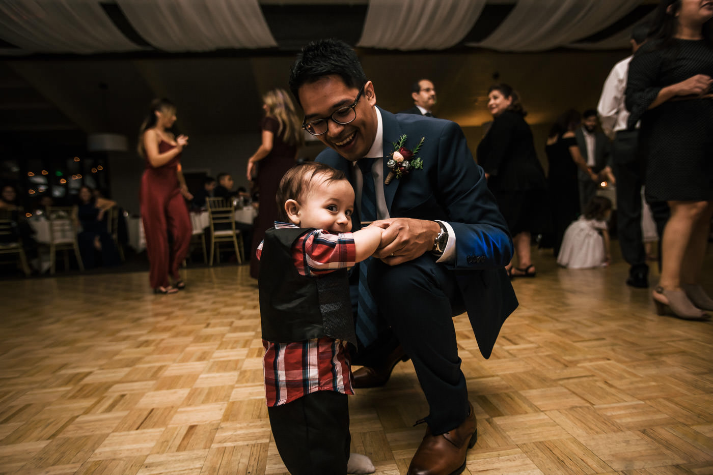Groom dances with baby at wedding reception.