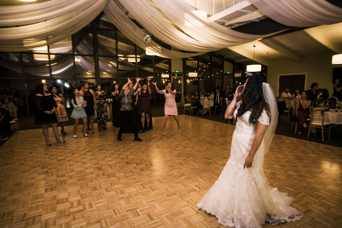 Bride throws weddign bouquet during reception at Knollwood Country Club wedding.