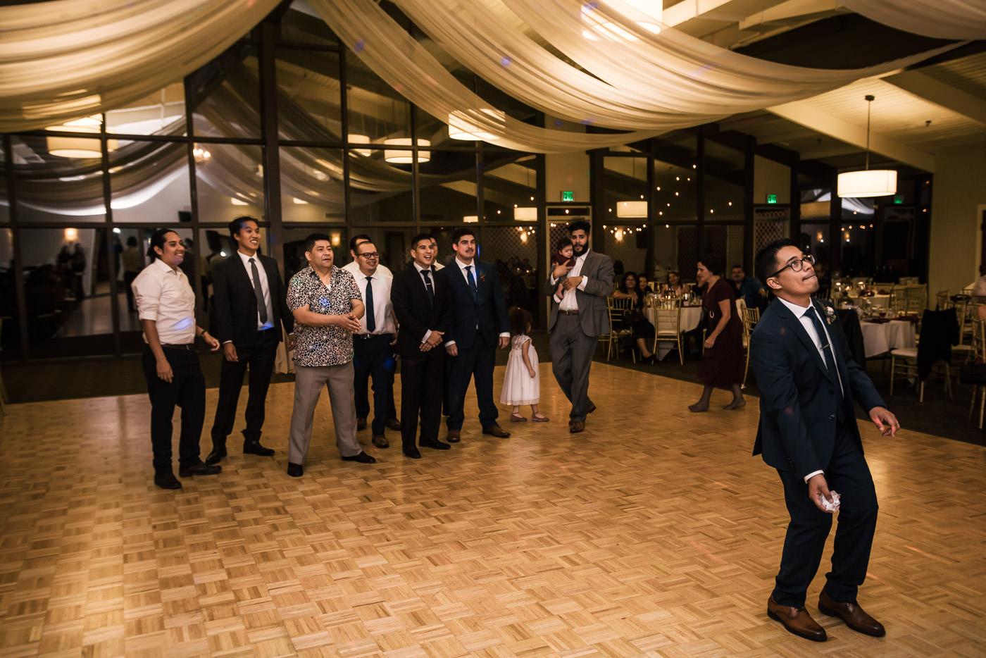 Groom prepares to throw the garter at wedding reception.