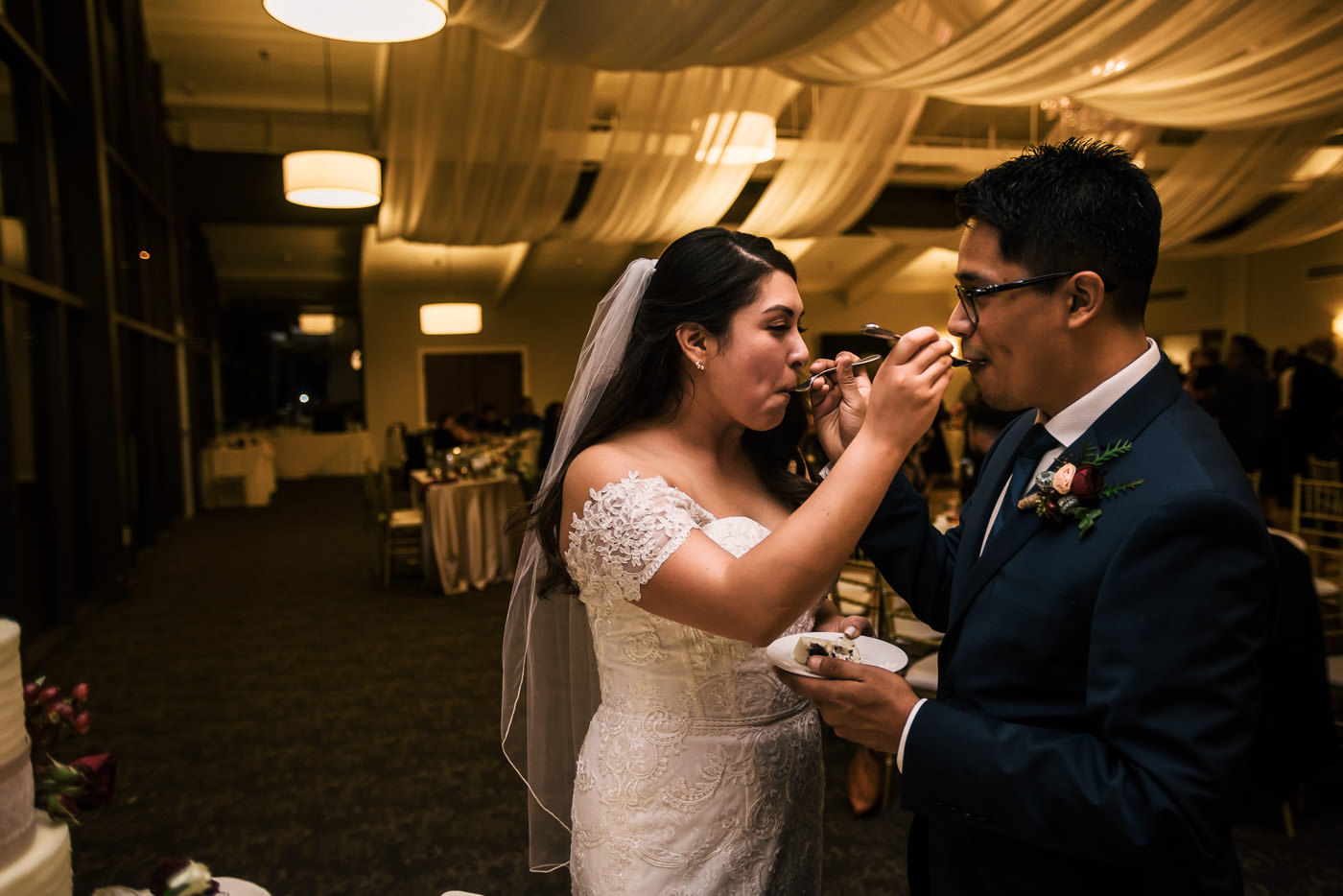 Bride and groom feed each other cake at their reception.
