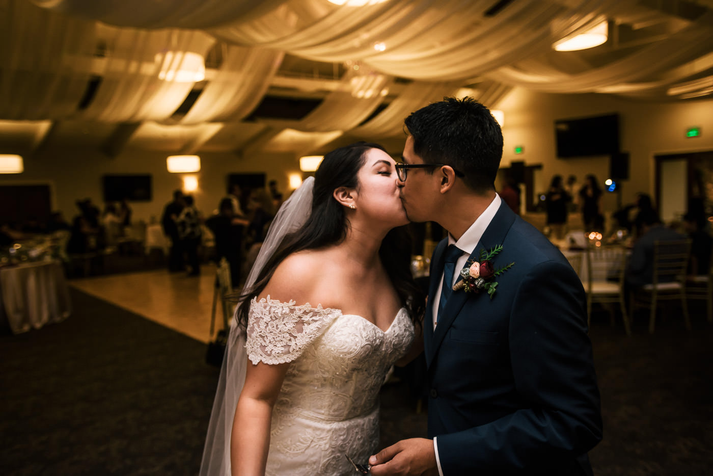 Couple kisses after their cake cutting at wedding reception.