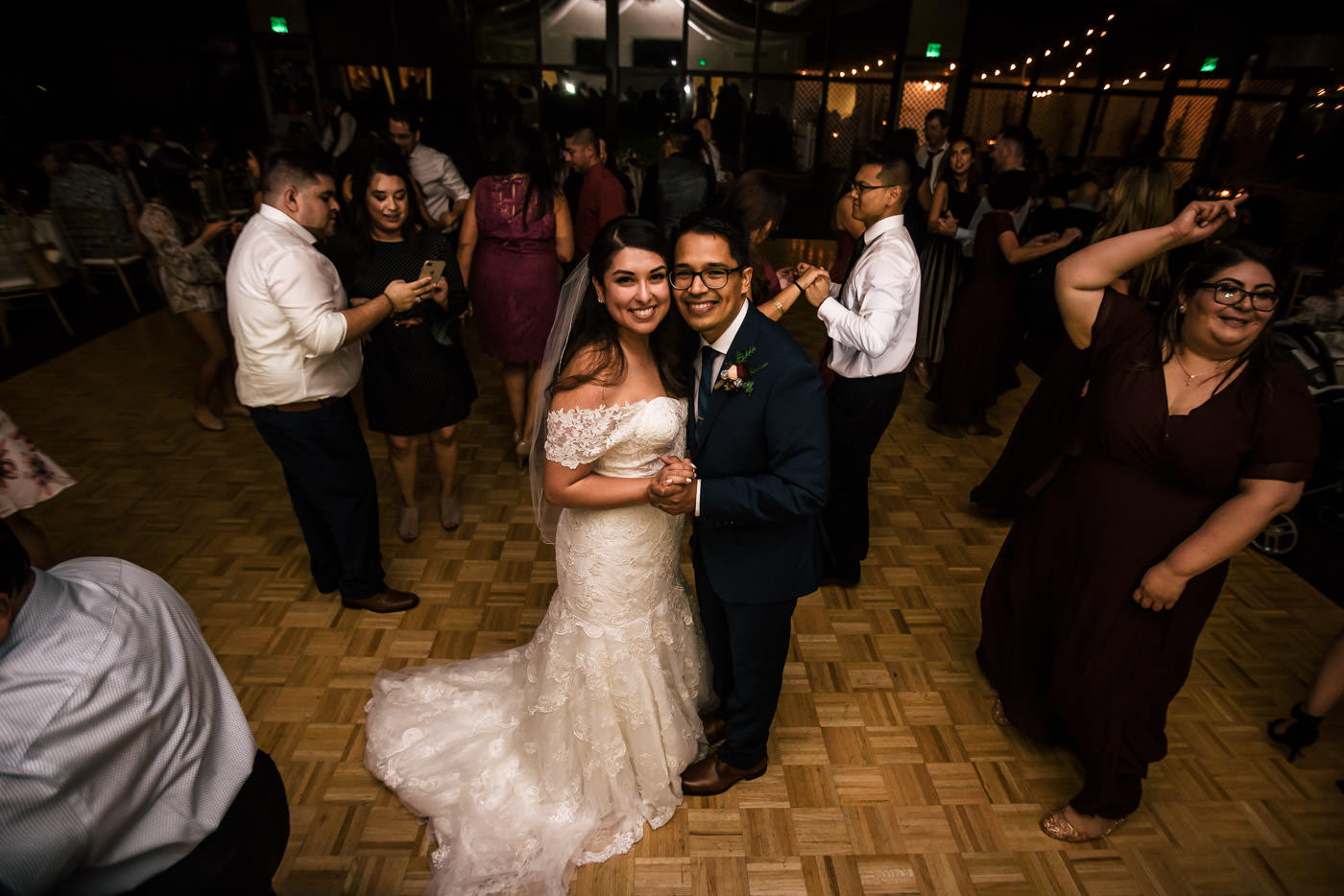 Couple smiles as they hit the dance floor with their guests at the reception.