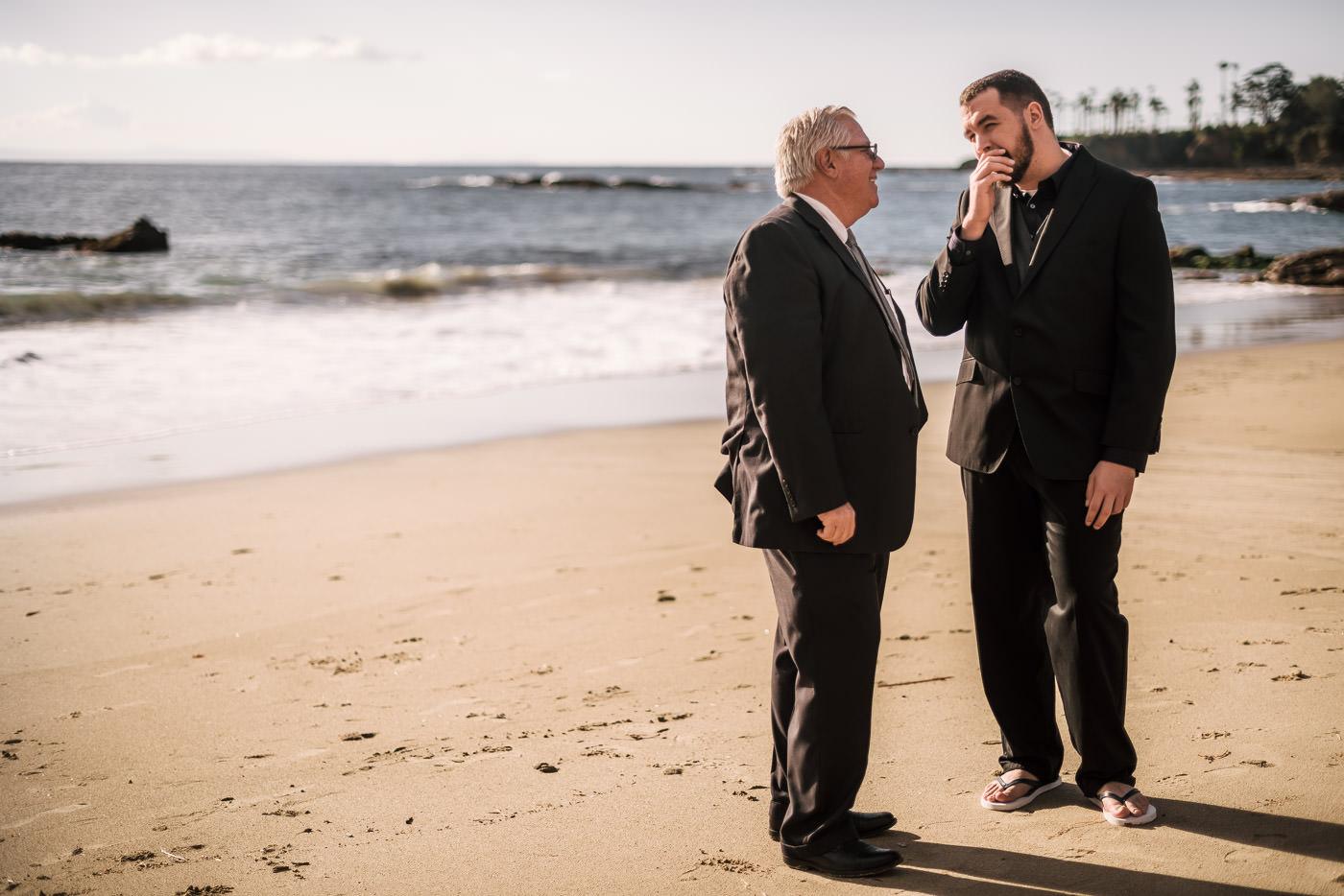 Groom talks with the minister on the sand at Laguna Beach.