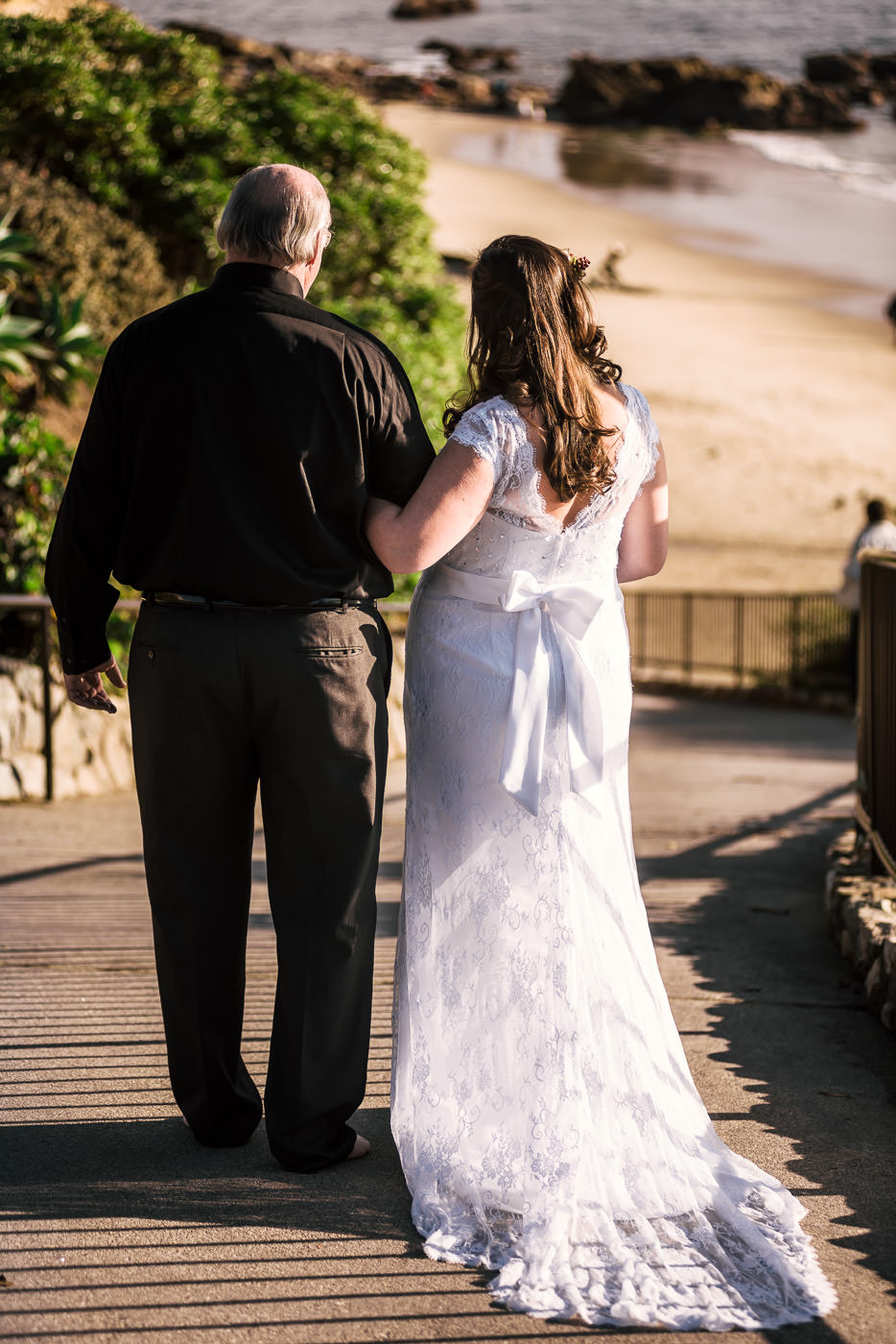 Father of the bride walks his daughter down to the ceremony at Laguna Beach.