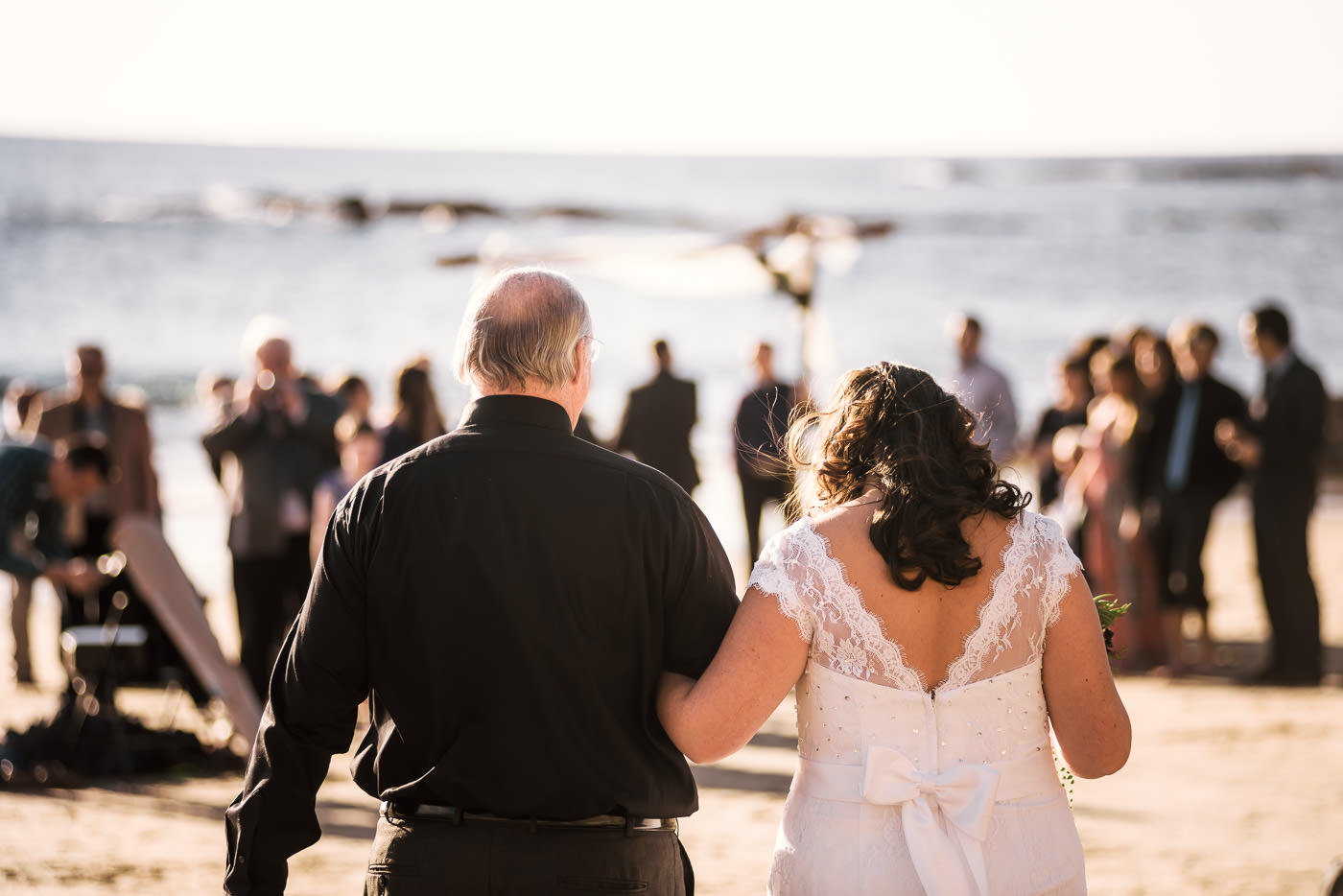 Bride is overcome with emotion as she walks across the sand to her wedding ceremony.