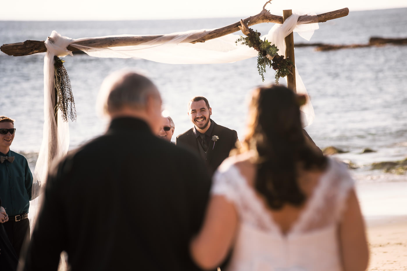 Groom smiles with joy as he sees his wife for the first time at their intimate beach elopement