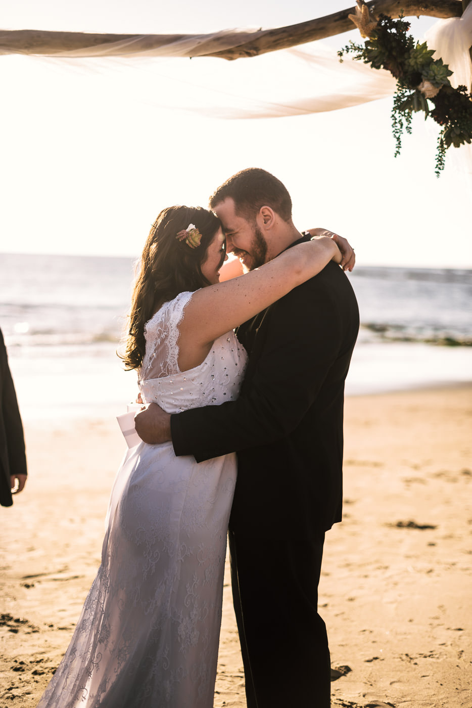 Newly married couple stare deeply into each others eyes after their wedding at Laguna Beach.