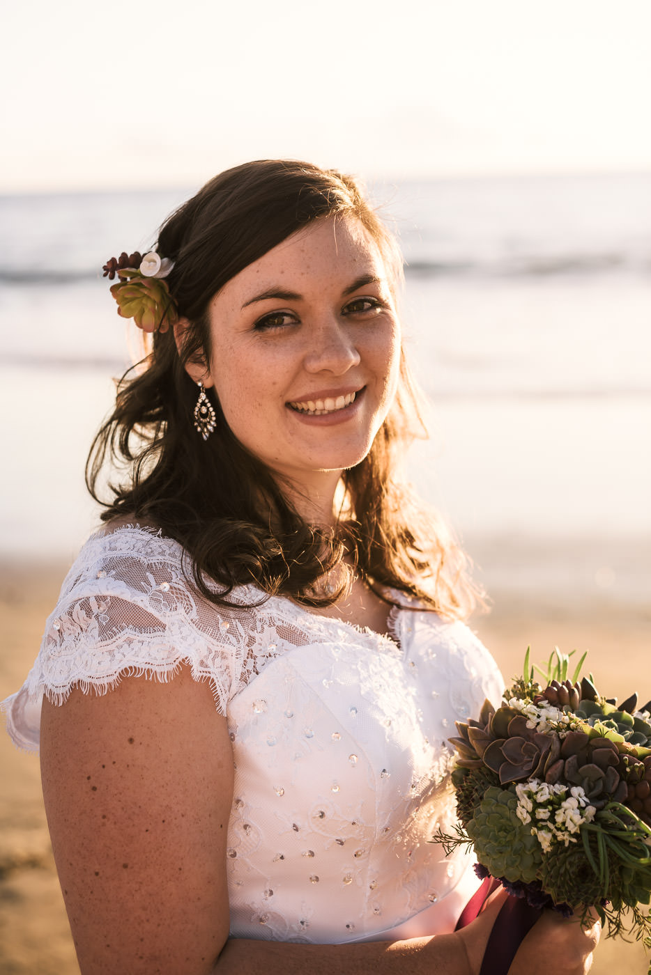 Happy bride lit by the Golden light of a sunset on Laguna Beach.