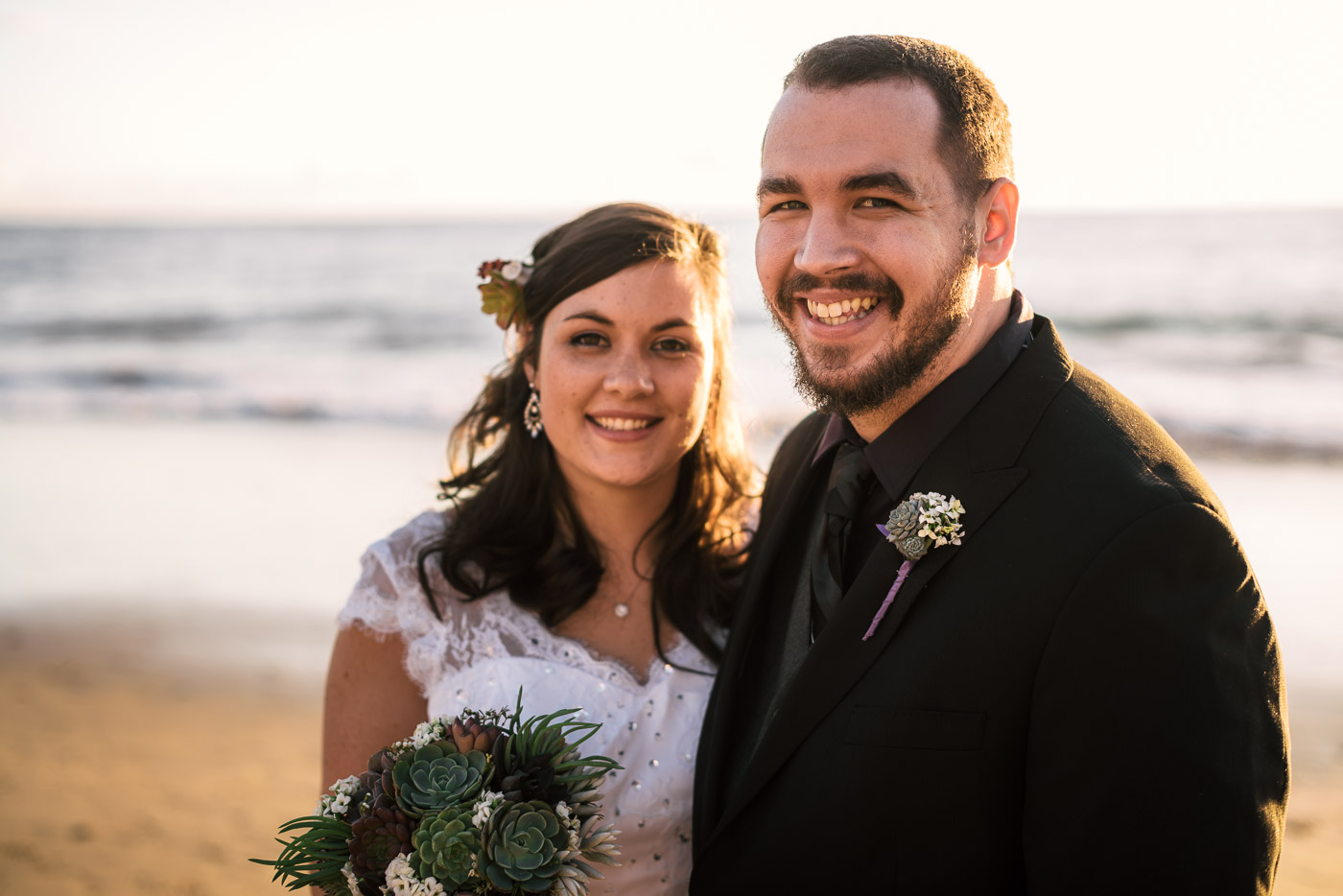 Happy newlywed couple smiles for the camera after their Laguna Beach wedding.