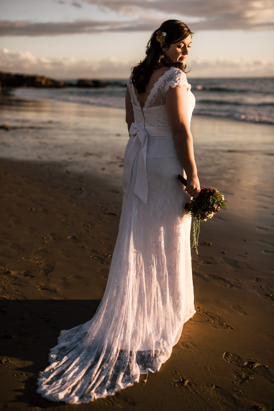 beautiful bride poses on the beach at sunset in her stunning dress after the intimate elopement