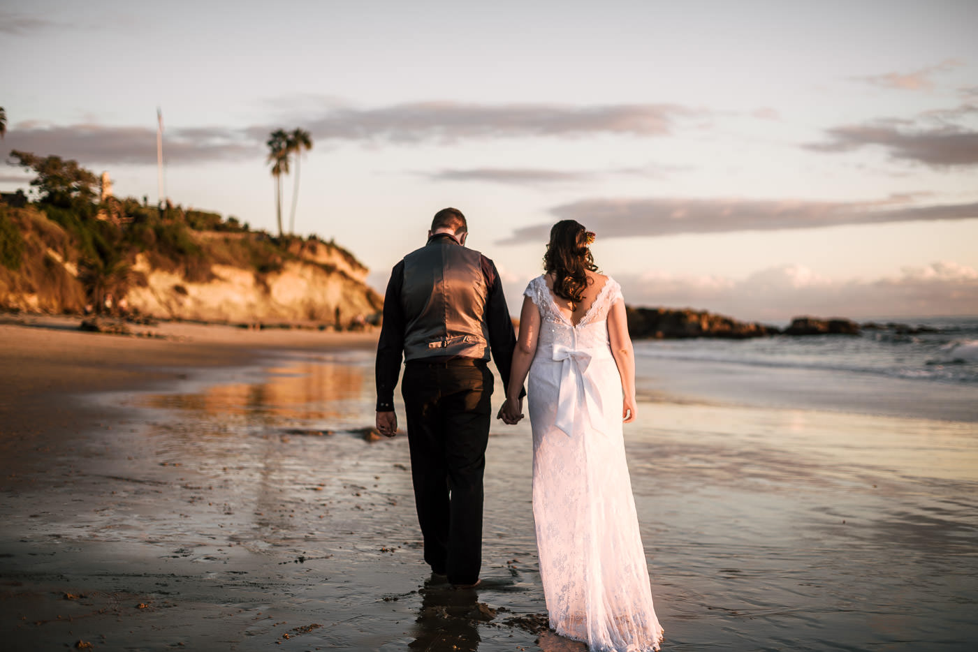 Couple walks barefoot in the wet sand after their Laguna Beach wedding.