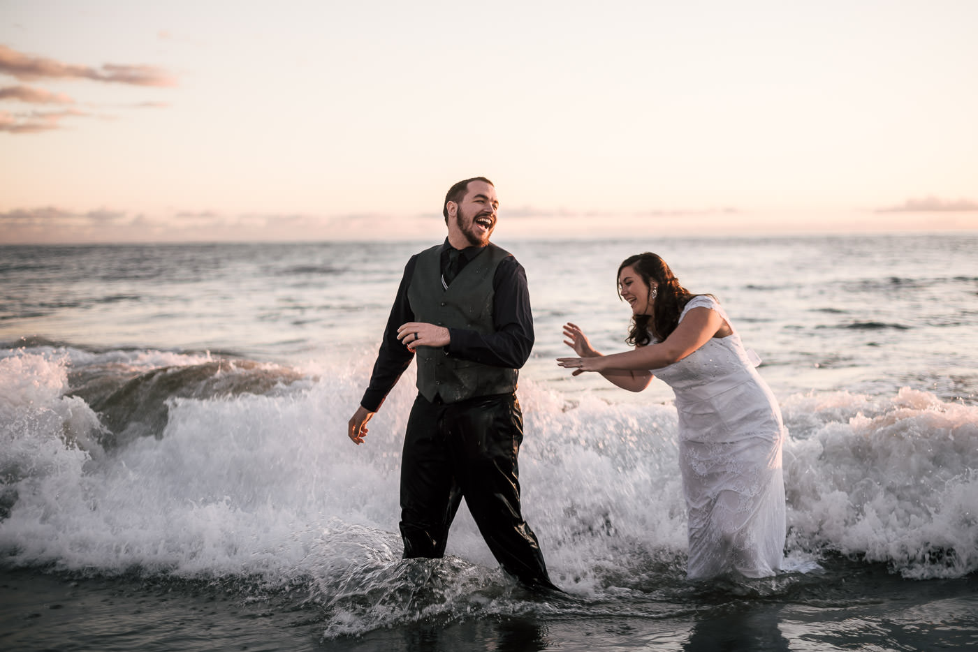 Bride chases groom through the crashing waves at their intimate Laguna Beach elopement at sunset.