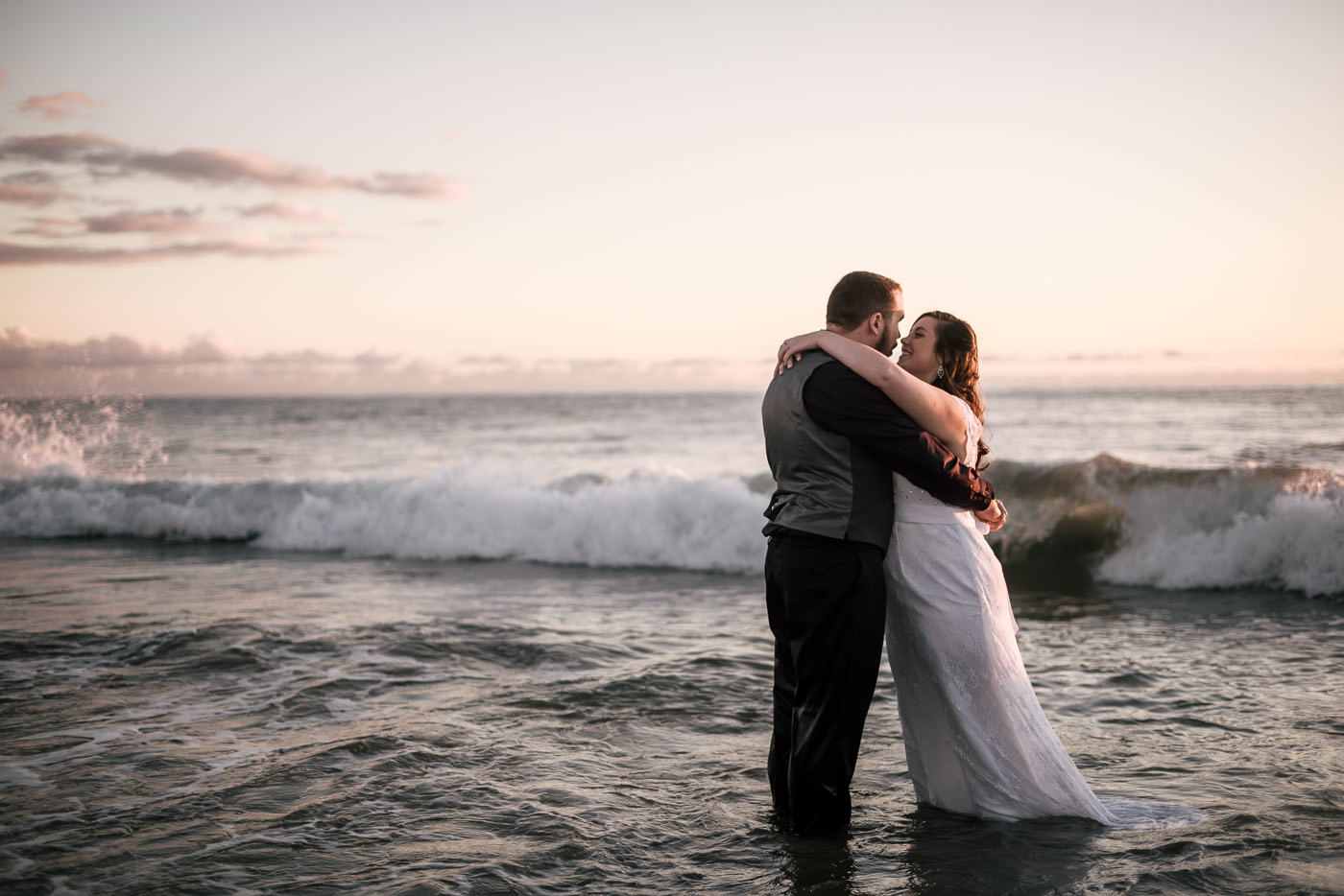 Couple stands in the ocean as waves crash around them at sunset after their wedding at Laguna Beach.