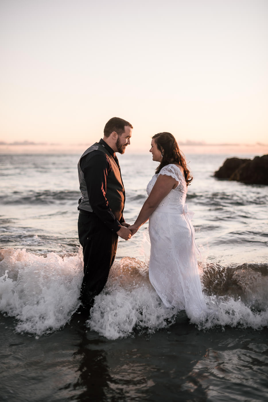 Couple gets in the ocean for some spectacular photos at sunset in Laguna Beach after their intimate wedding.