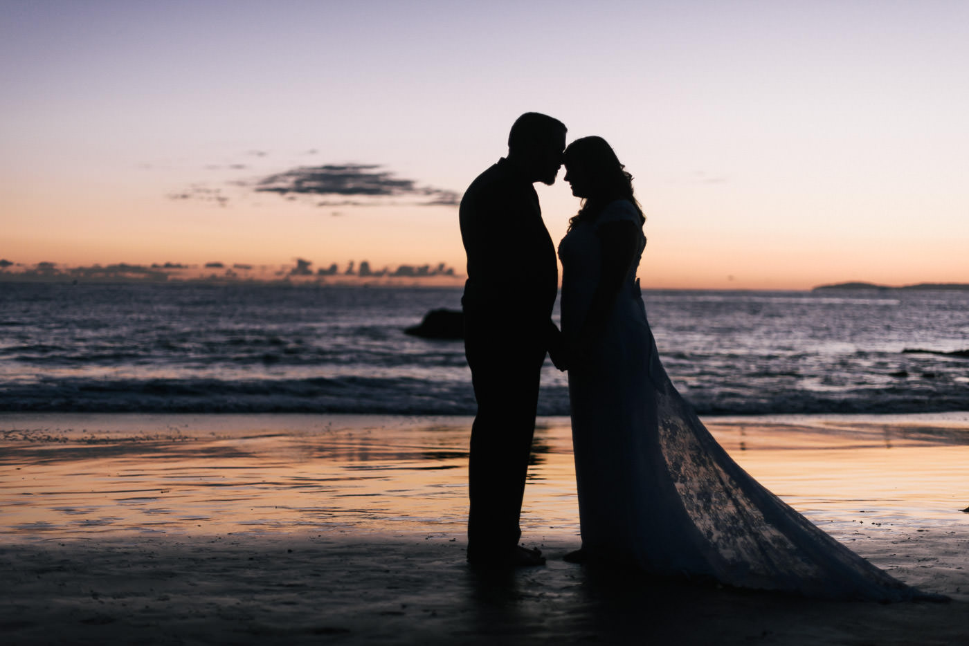 Sillhouetted couple gets close for a stunning wedding photo in Laguna Beach.