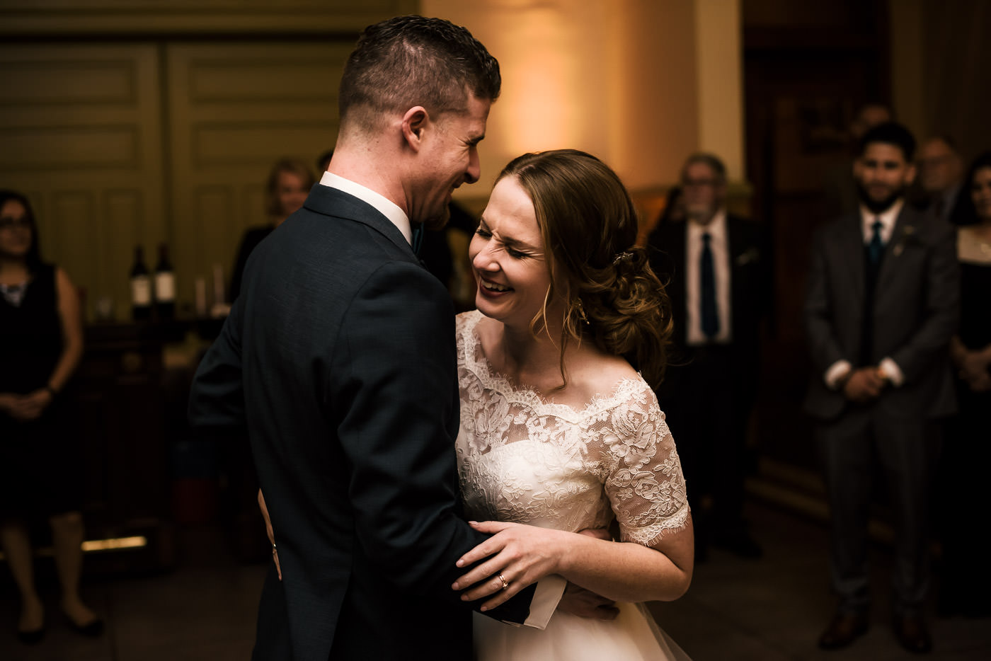 Bride and groom laugh as they dance for the first time as husband and wife.