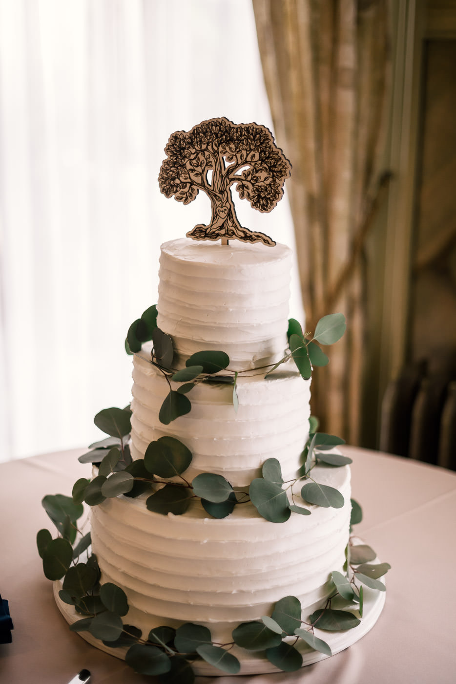 Beautiful tierd wedding cake with eucalyptus details and an oak tree topper.