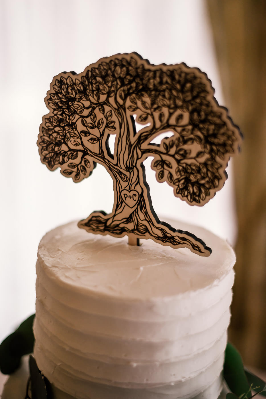 Wooden tree cake topper with couples initials carved in the trunk.