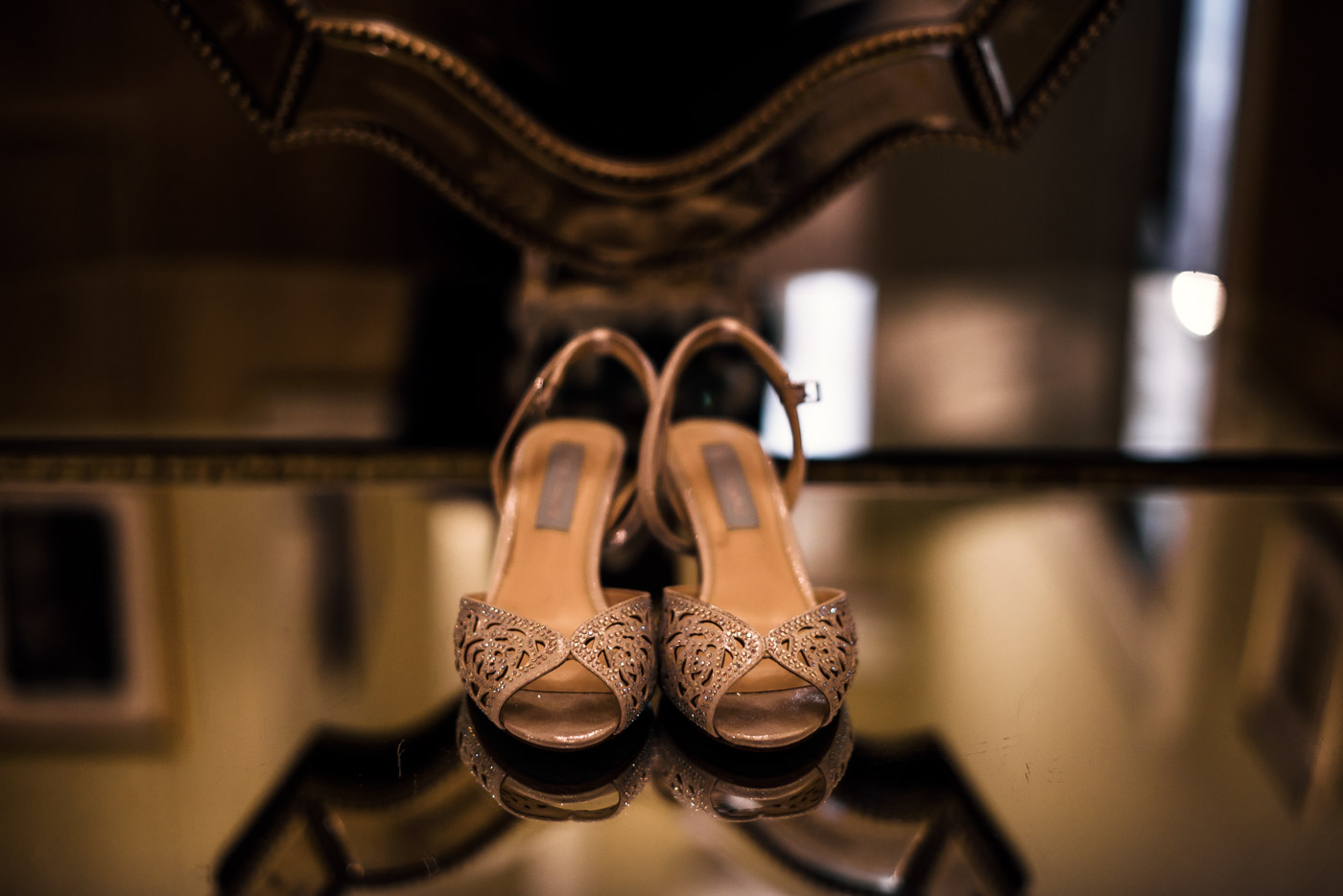 Brides wedding shoes reflected in a mirrored table at the Castle Green in Pasadena.