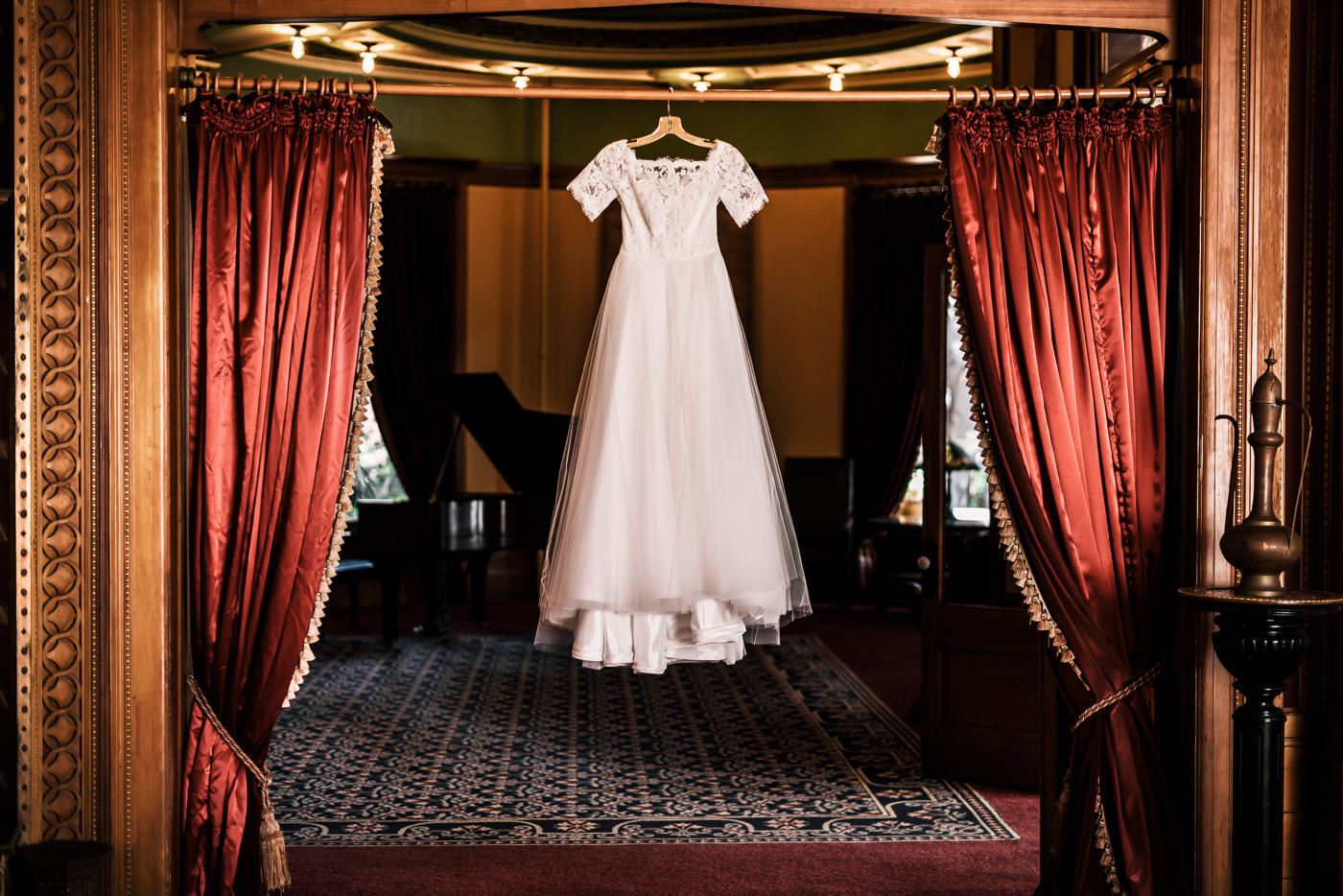 Vintage styled wedding dress hangs in the Historic lobby of the Castle Green in Pasadena California