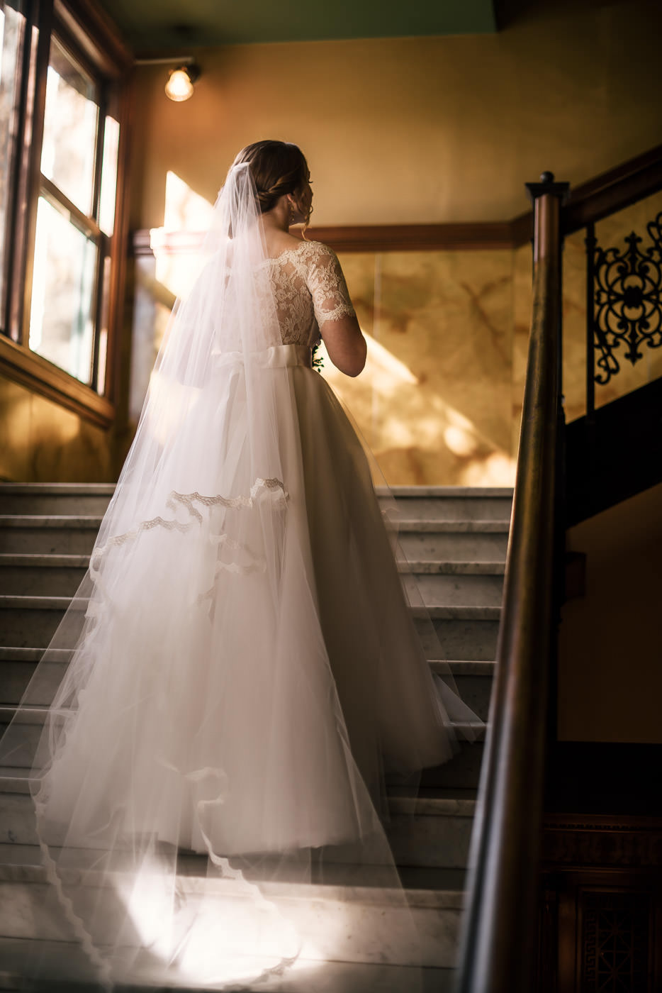 Bride heads up the marble staircase of the Castle Green for her first look.