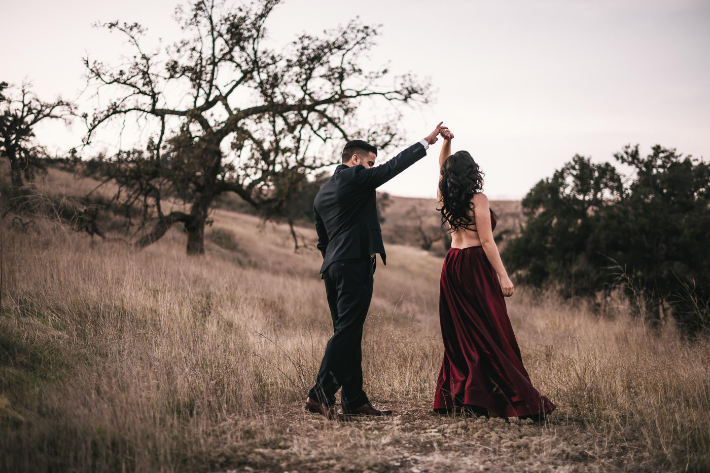Soon to be groom twirls his future wife in the fields of Malibu.