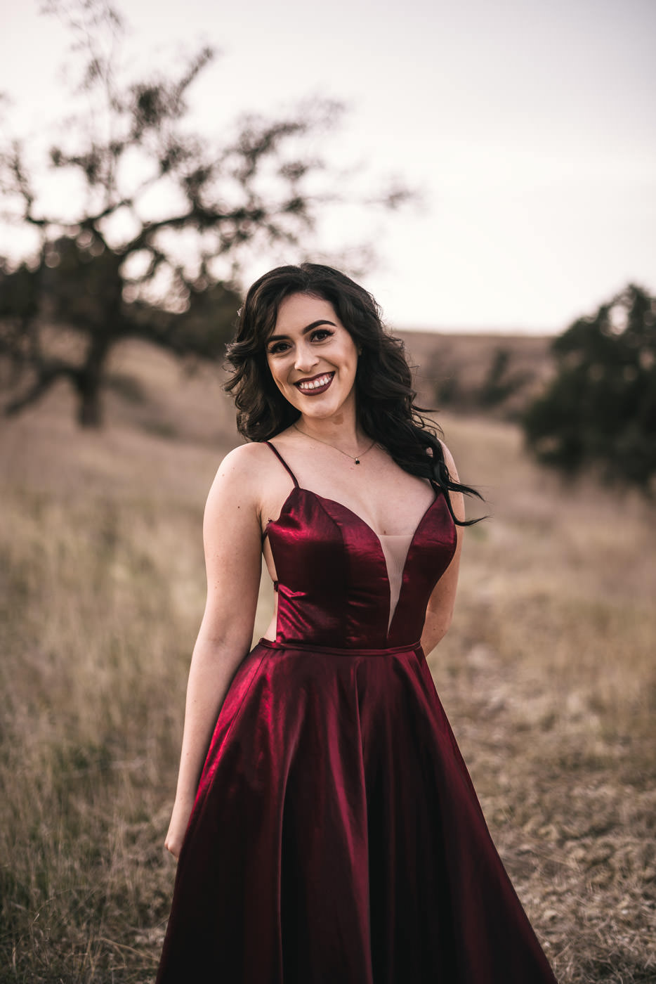 Beautiful bride to be wears a shimmering red dress to her engagment session.