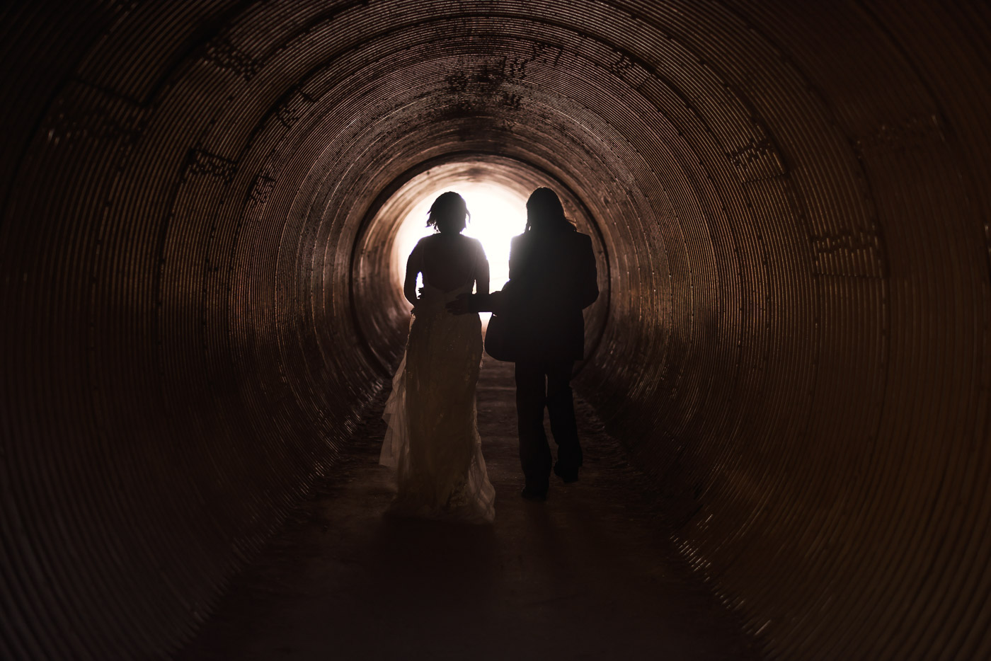 Couple is silhouetted by the light at the end of the tunnel at Julia Pfeiffer Burns State Park during their intimate elopement.