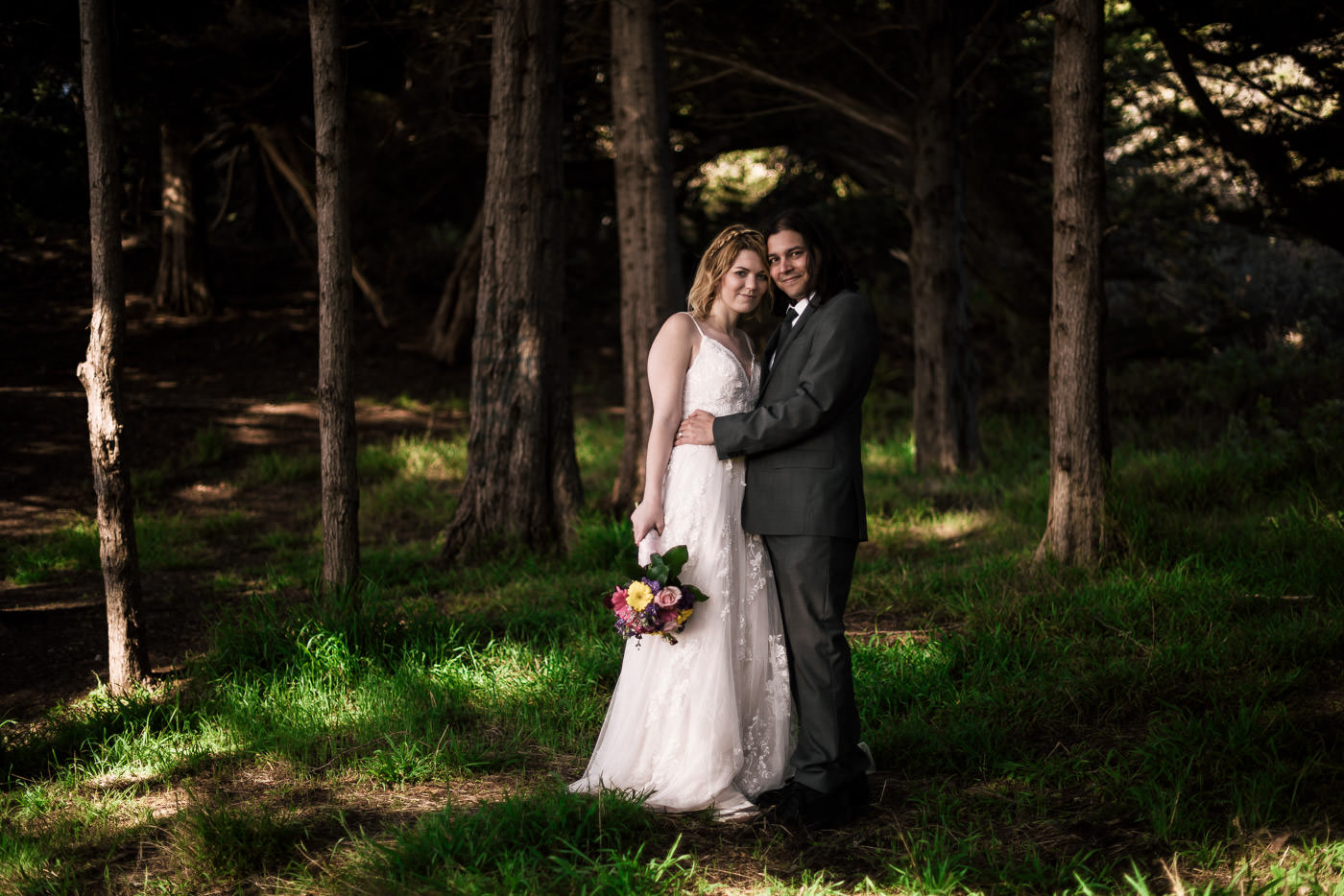 Couple smiles for the camera among the wooded coastline of Big Sur for a classic wedding photo.