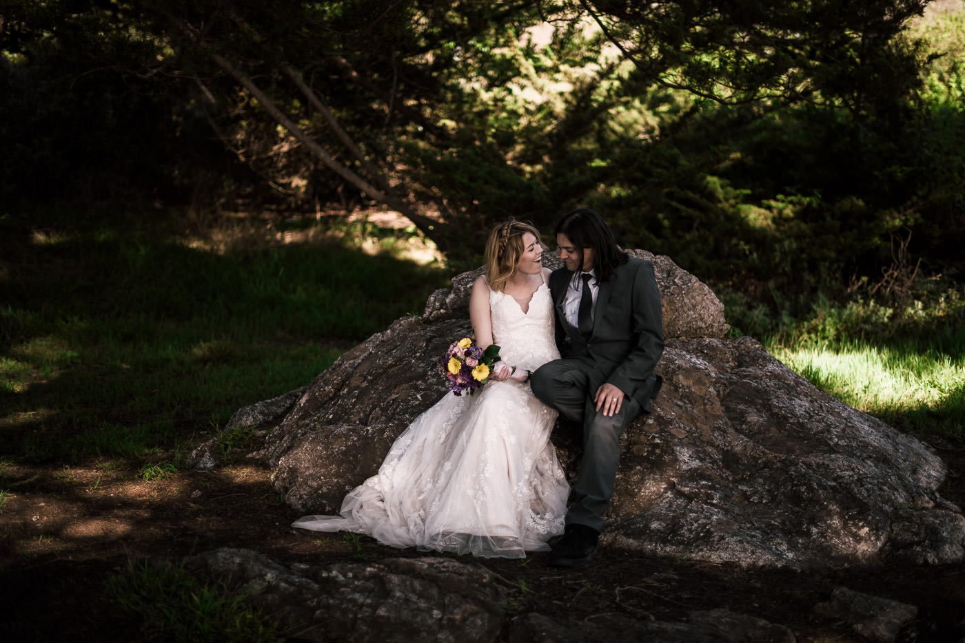 Bride and groom sit for a moment on a large rock under a grove of coastal trees during their forest elopement in Big Sur.