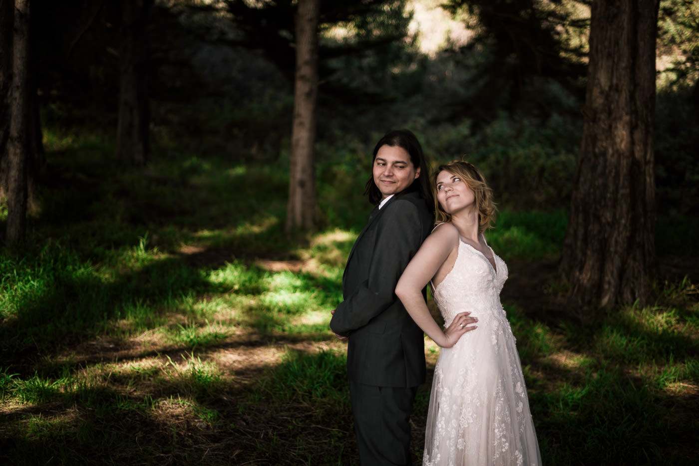 Newly weds stand back to back under the trees for their elopement photographer.