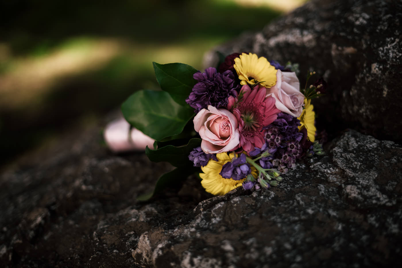 Colorful wedding bouquet sits on a rock in Big Sur.