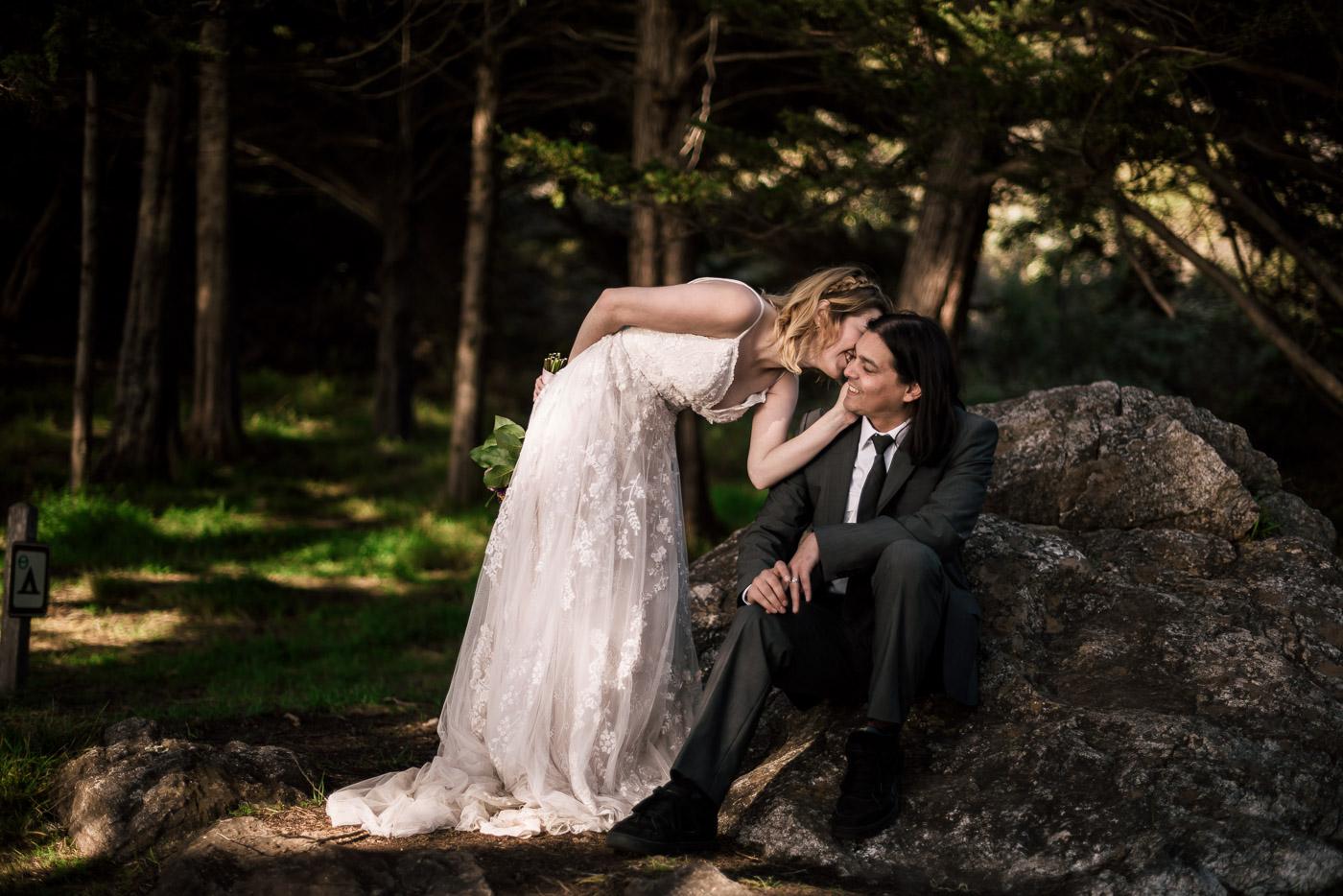 Loving bride whispers in her husbands ear.