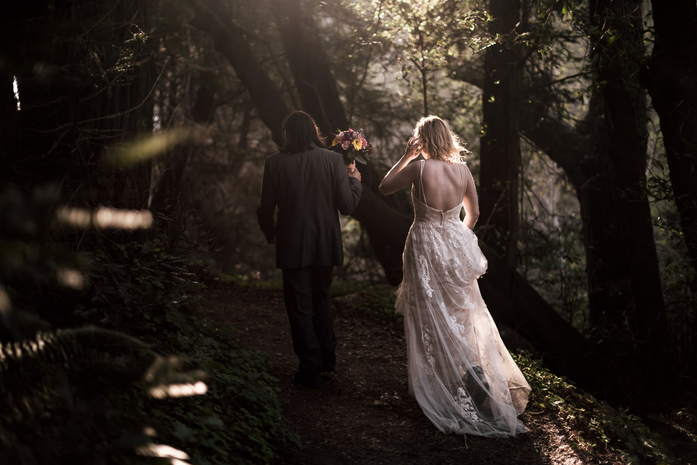 Newly married pair wnaders through the woods at sunset.