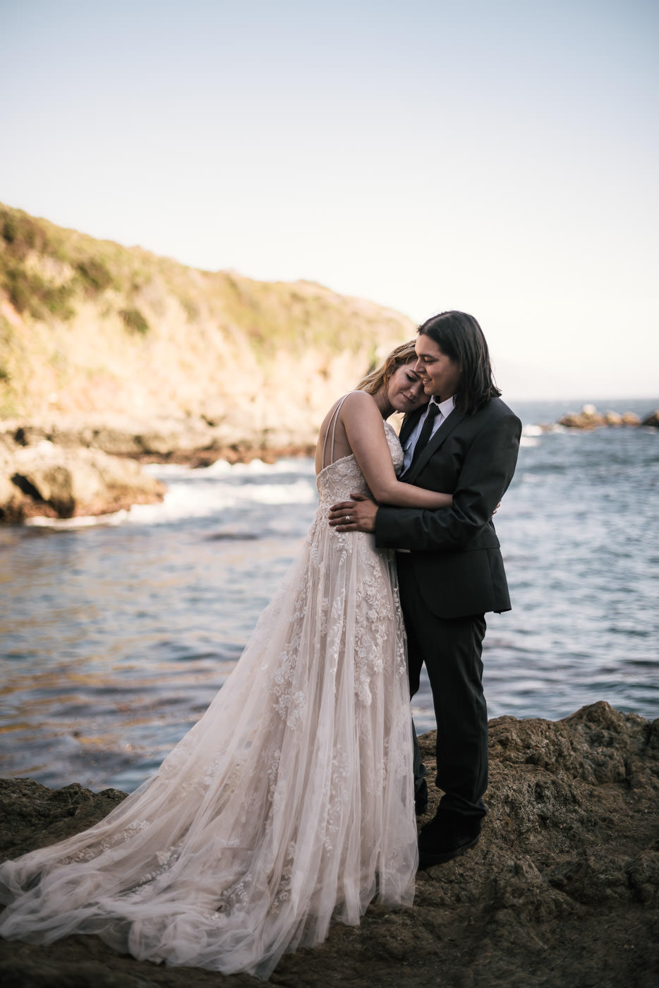 Two lovers have a romantic moment on the rocky shores of Big Sur after their intimate wedding.